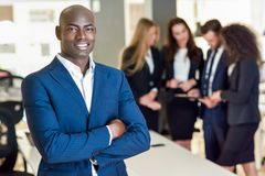Businessman leader in modern office with businesspeople working. Black businessman leader looking at camera in modern office with multi-ethnic businesspeople stock photo