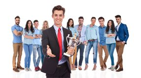 Businessman leader with trophy greeting you with a handshake. Businessman group leader with trophy greeting you with a handshake to his casual team while he is royalty free stock images