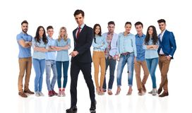 Businessman leader walks to side while his team is behind. Businessman group leader walks to side while his casual team is standing behind him on white stock photography