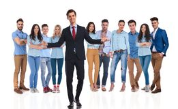 Businessman leader welcomes you with both hands in his team. Smiling businessman team leader welcomes you with both hands in his casual team while standing on stock photo