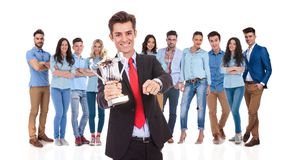 Businessman leader of winning team pointing at you. Businessman leader of winning casual team pointing at you while holding a trophy and standing on white royalty free stock photography