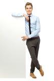 Businessman leaning against blank billboard Royalty Free Stock Image