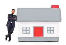 Businessman leaning against a miniature house Stock Photo
