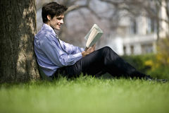 A businessman leaning against a tree, reading a book royalty free stock photo