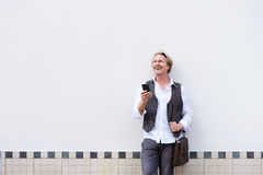 Businessman leaning against wall with mobile phone Stock Photography