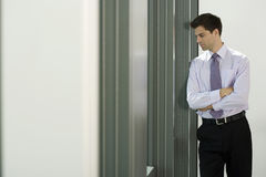 Businessman leaning against wall in office, looking through window, thinking, side view Royalty Free Stock Photography