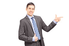 Businessman leaning against wall and pointing Stock Images