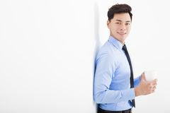 Businessman leaning against white wall in office Stock Photo