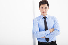 businessman leaning against white wall in office Royalty Free Stock Images