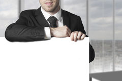 Businessman leaning on blank sign Royalty Free Stock Photos