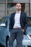 Businessman leaning on car Royalty Free Stock Image