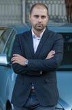 Businessman leaning on car Stock Photos
