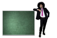 Businessman leaning on the chalkboard Stock Photo