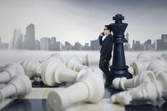 Businessman Leaning at Chess Figures Stock Photos