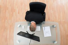 Businessman Leaning On Computer Keyboard Stock Photography