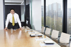 Businessman Leaning At Conference Table Royalty Free Stock Photography