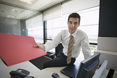 Businessman leaning on desk in office, passing red file, smiling, portrait stock photos