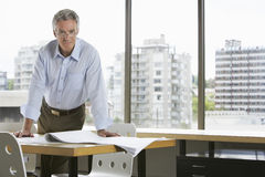 Businessman Leaning On Desk In Office Royalty Free Stock Photography