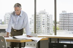 Businessman Leaning On Desk In Office Royalty Free Stock Photos