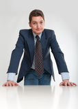 Businessman leaning on a desk Royalty Free Stock Image