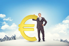 Businessman leaning on euro sign Royalty Free Stock Image