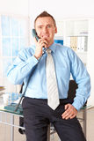Businessman leaning on office desk with phone Royalty Free Stock Images
