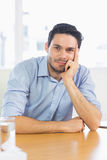 Businessman leaning on office desk Stock Photo