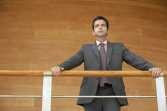Businessman Leaning On Railing Standing Against Wooden Wall Stock Photo