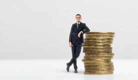 Businessman leaning on stack of big golden coins Stock Photos