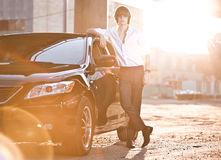 businessman leaning to luxury black car at sunset rays Stock Images