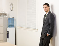 Businessman leaning on wall Stock Images