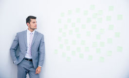 Businessman leaning on the wall Stock Images