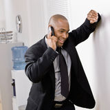 Businessman leaning on wall talking on cell phone Stock Images
