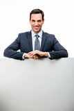 Businessman leaning on a white placard Royalty Free Stock Images