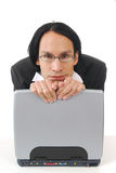 Businessman leaningon compuer. A businessman resting his head on the back of his laptop Royalty Free Stock Image