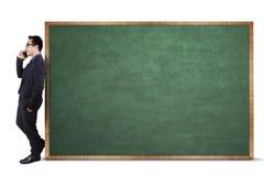 Businessman leans on empty blackboard Stock Photography