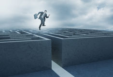 Businessman leaping above a maze Royalty Free Stock Photos