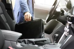 Businessman with leather briefcase sits on driver seat in car with modern interior stock images