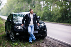 Businessman in leather jacket standing near car Stock Photos