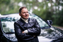 Businessman in leather jacket standing near car Stock Photography