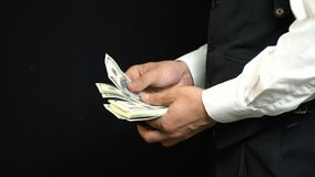 A businessman in a suit pulls out of his pocket a leather purse in which a bundle of one hundred dollar bills stock video
