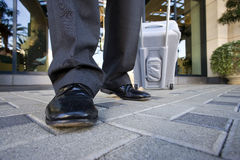 Businessman leaving hotel with luggage, low section, front view, surface level Royalty Free Stock Image