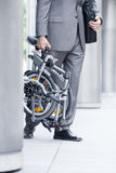 Businessman leaving office building, carrying folding commuter bicycle, side view, low section Stock Images