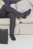 Businessman with legs crossed on couch Royalty Free Stock Photo