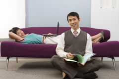 Businessman with legs crossed on floor by woman lying on sofa using laptop, smiling, portrait. Businessman with legs crossed on floor by women lying on sofa Stock Images