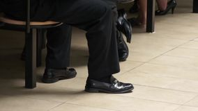 Businessman legs sit on the chair Stock Photography