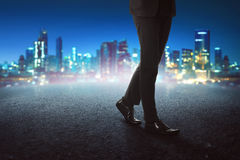 Businessman legs wearing black shoes walking on concrete. With cityscape background Stock Photography
