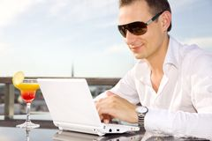 Businessman on leisure with laptop and cocktail Royalty Free Stock Images