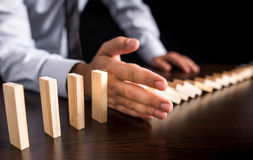 Businessman Letting Or Preventing  Dominoes Chain Toppling Royalty Free Stock Photo