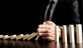 Businessman Letting Or Preventing  Dominoes Chain Toppling Stock Photography